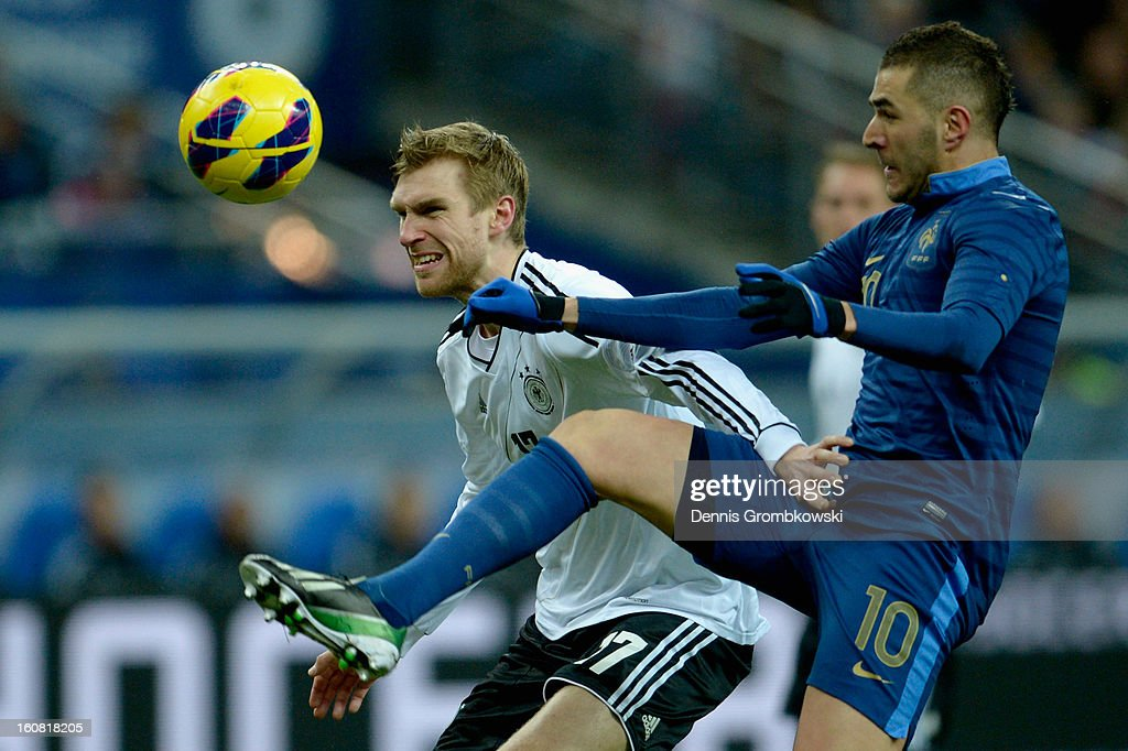 Per Mertesacker of Germany challenges Karim Benzema of France during the international friendly match between France and Germany at Stade de France on February 6, 2013 in Paris, France.