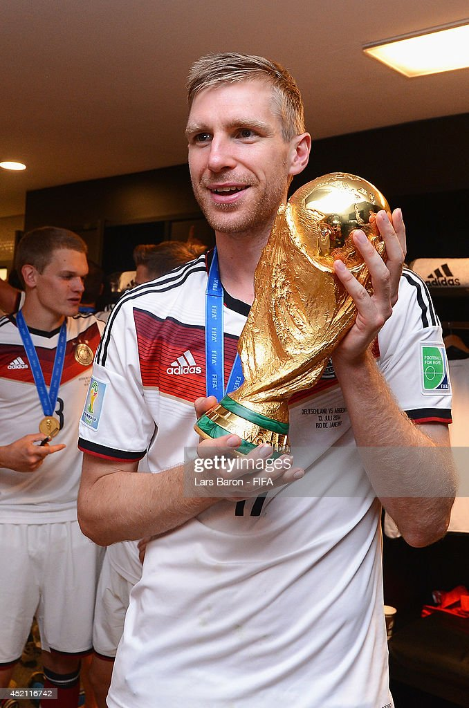 <a gi-track='captionPersonalityLinkClicked' href=/galleries/search?phrase=Per+Mertesacker&family=editorial&specificpeople=207135 ng-click='$event.stopPropagation()'>Per Mertesacker</a> of Germany holds up the World Cup trophy in the Germany dressing room after the 2014 FIFA World Cup Brazil Final match between Germany and Argentina at Maracana on July 13, 2014 in Rio de Janeiro, Brazil.
