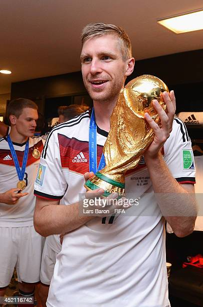Per Mertesacker of Germany holds up the World Cup trophy in the Germany dressing room after the 2014 FIFA World Cup Brazil Final match between...