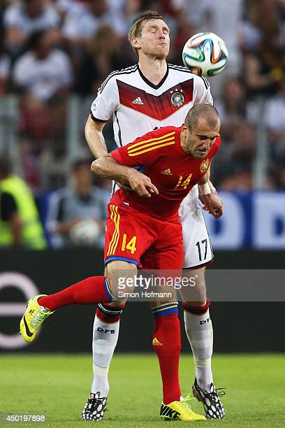 Per Mertesacker of Germany is challenged by Yura Movsisyan of Armenia during the International Friendly match between Germany and Armenia at Coface...