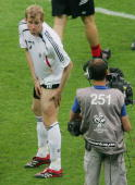 Per Mertesacker of Germany shows off his leg following a scuffle between the two sides at the end of the FIFA World Cup Germany 2006 Quarterfinal...