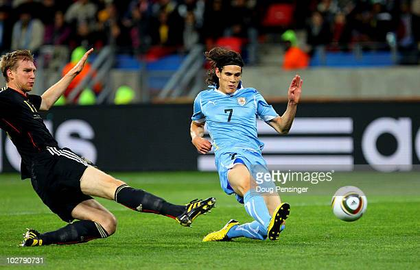 Per Mertesacker of Germany tries to defend as Edinson Cavani of Uruguay scores his team's first goal during the 2010 FIFA World Cup South Africa...