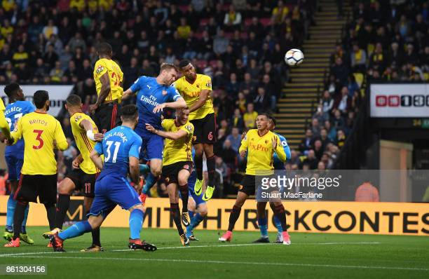 Per Mertesacker outjumps Watford defender Adrian Mariappa to score for Arsenal during the Premier League match between Watford and Arsenal at...