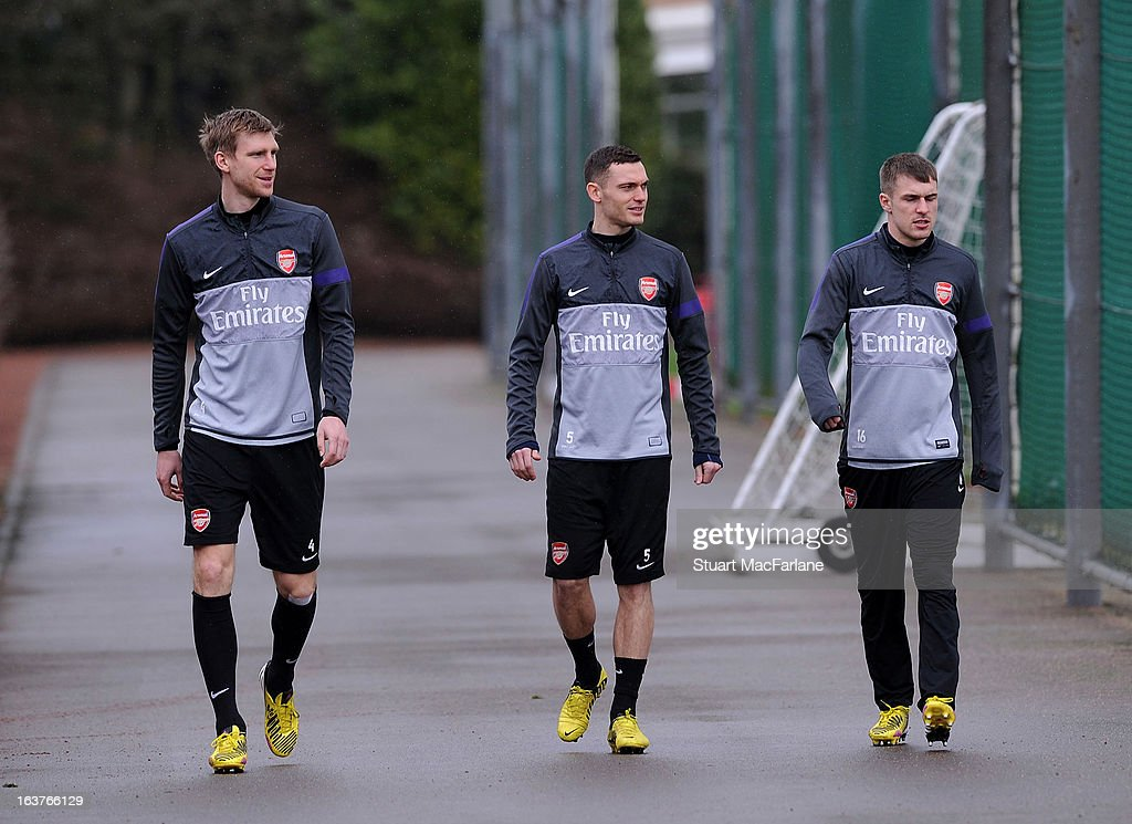 Per Mertesacker, Thomas Vermaelen and Aaron Ramsey of Arsenal before a training session at London Colney on March 15, 2013 in St Albans, England.