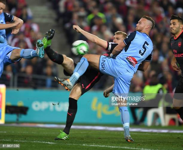 Per Mertesaker shoots past Sydney FC defender Jordy Buijs to score the 1st Arsenal goal during the preseason friendly match between Sydney FC and...