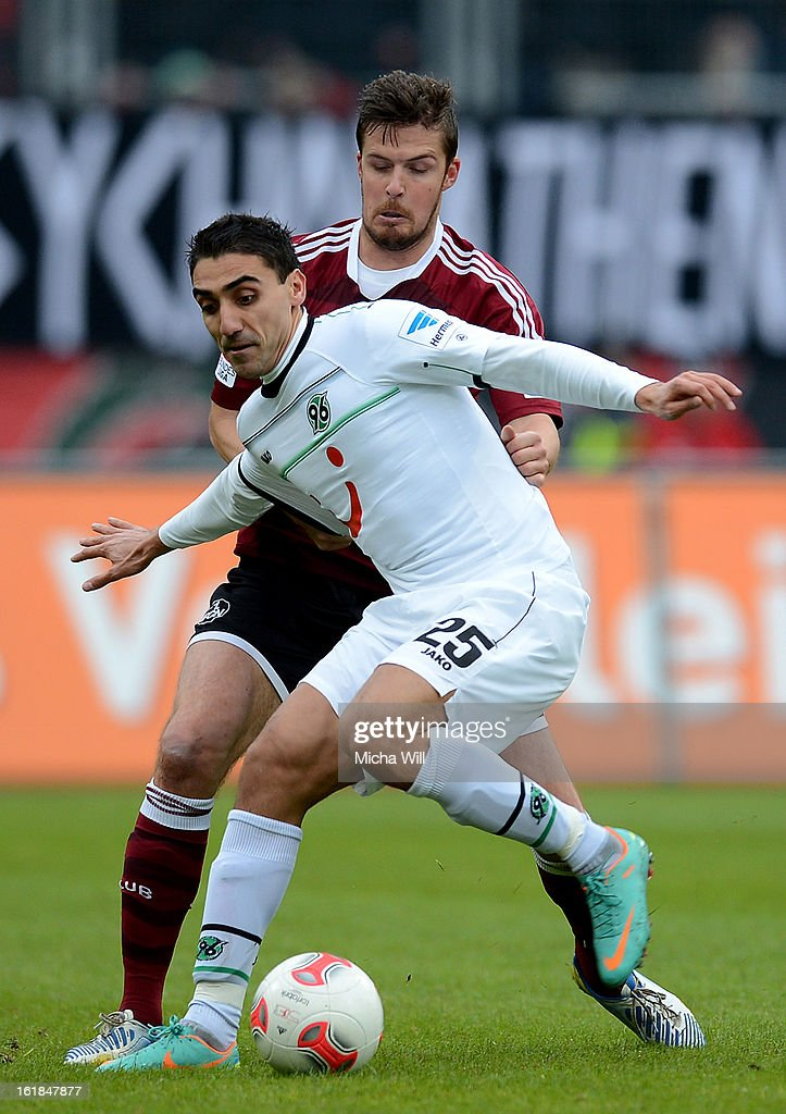 Per Nilsson (back) of Nuernberg challenges Mohammed Abdellaoue of Hannover during the Bundesliga match between 1. FC Nuernberg and Hannover 96 at Grundig-Stadion on February 17, 2013 in Nuremberg, Germany.