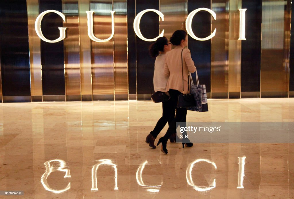 This picture taken on November 9, 2013 shows Chinese shoppers walking past a Gucci shop in Nanjing, east China's Jiangsu province. Official data last month showed China's economy -- the world's second largest and a key driver of regional and global growth -- expanded 7.8 percent in July-September, snapping a two-quarter slowdown. CHINA OUT AFP PHOTO