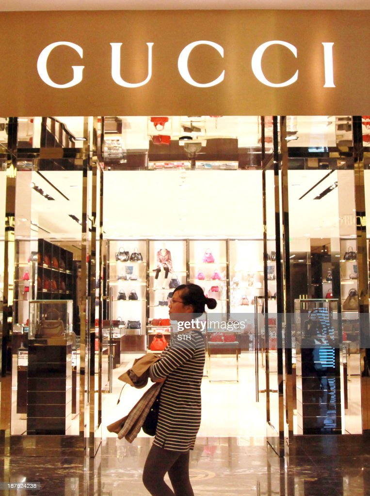This picture taken on November 9, 2013 shows a Chinese shopper walking pass a Gucci shop in Nanjing, east China's Jiangsu province. Official data last month showed China's economy -- the world's second largest and a key driver of regional and global growth -- expanded 7.8 percent in July-September, snapping a two-quarter slowdown. CHINA