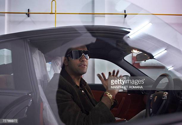 TO GO WITH 'INDIAECONOMYSOCIETY' In this picture taken 05 December 2006 Indian businessman Rajeev Sen gestures as he chats with a Porsche executive...