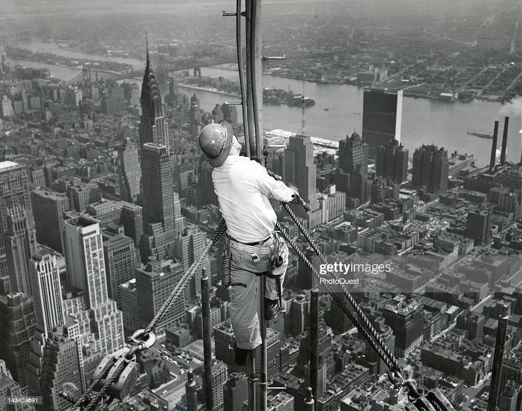 Perched some 1200 feet above the ground, Ray Corbett fastens lines of the temporary television antenna atop the Empire State Building, New York, New York, 1950. The tall building at left is the 1046-foot-high Chrysler Building. The UN Secretariat Building can be seen in the upper right.