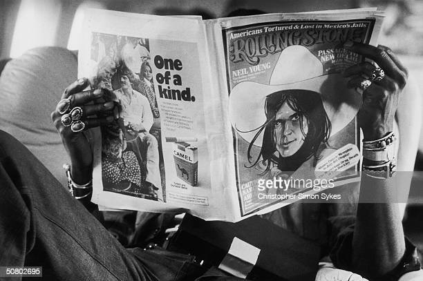 Percussionist Ollie Brown relaxes on the plane with a copy of Rolling Stone magazine during the Rolling Stones Tour of the Americas 1975