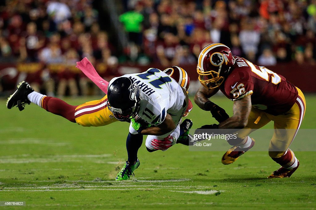 Percy Harvin of the Seattle Seahawks is tackled by Perry Riley of the Washington Redskins at FedExField on October 6 2014 in Landover Maryland