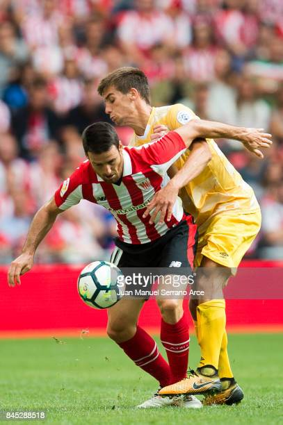 Pere Pons of Girona FC competes for the ball with Aritz Aduriz of Athletic Club during the La Liga match between Athletic Club and Girona at on...