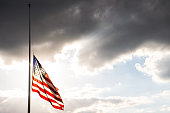 Perfect American Flag lowered to Half-Mast waving in the wind fully extended after another sad memorial the flag glowing illuminated by bright sunshine