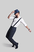 Full length of handsome young man in suspenders adjusting his hat and making a face while dancing against grey background