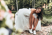Attractive young woman in wedding dress putting on sports shoes and smiling while sitting on the swing outdoors