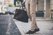 Close-up of man holding leather bag while walking outdoors