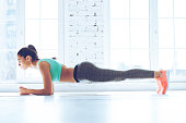 Full-length side view of young beautiful woman in sportswear doing plank while standing in front of window at gym