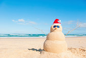 Snowman at the beach with sun glasses. The shells for mouth and buttons have been removed in this shot