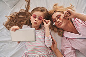 Top view of young beautiful mother and her cute daughter taking selfie with smart phone and smiling while lying on the bed at home