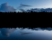 The sky, clouds and forest line in the Swedish nature preserve of Tyresta reflects in a calm forest lake in perfect symmetry