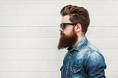 Side view of young bearded man in eyewear looking away while standing outdoors