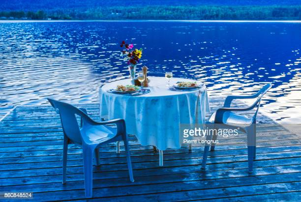 Perfectly romantic dinner set up on a blue lake at dusk - floating deck in summertime. British Columbia, Canada
