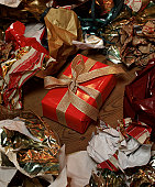Perfectly wrapped gift sits amongst debris of Christmas wrapping