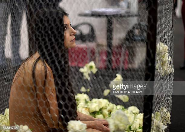 Performance art called 'The CageLa Gabbia' by Romina de Novellis during the VIP opening of The Armory Show 2016 in New York March 2 2016 / AFP /...