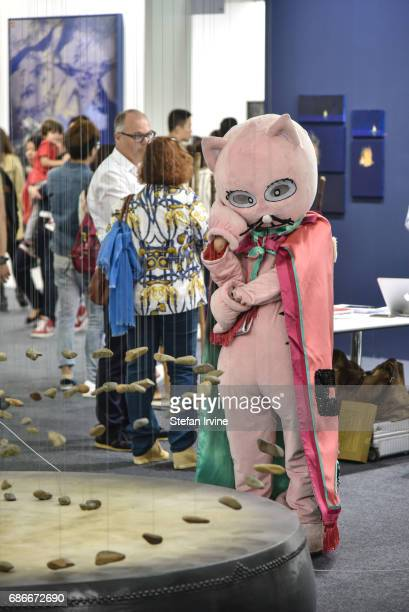 A performance artist dressed up in an oversize cat costume and selfstyled at 'China's No1 Art Critic' comtemplates an art installation at Art Central...
