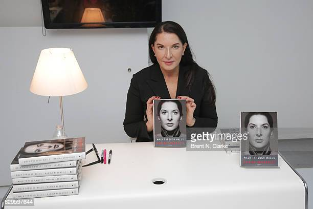 Performance artist Marina Abramovic poses with a copy of her memoir following a screening of her newest film 'Marina Abramovic In Brazil The Space In...