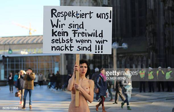 Performance artist Milo Moire holds up a poster reading 'Respect us We are no fair game even when we are naked' as she stands near Cologne's landmark...