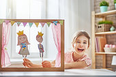 Happy girl plays with performance in the puppet theater with prince and princess at home. Funny lovely child is having fun in kids room.