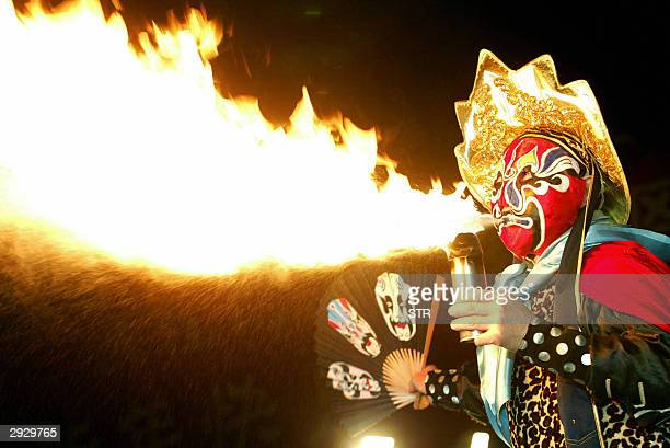 A performer blows fire during an entertainment program in Hangzhou 04 February 2004 for celebrations marking the Chinese Lantern Festival which falls...