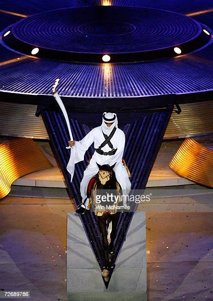 A performer carries the Asian Games torch while riding an Arabian horse during a rehearsal at Khalifa Stadium for the Opening Ceremony of the 15th...
