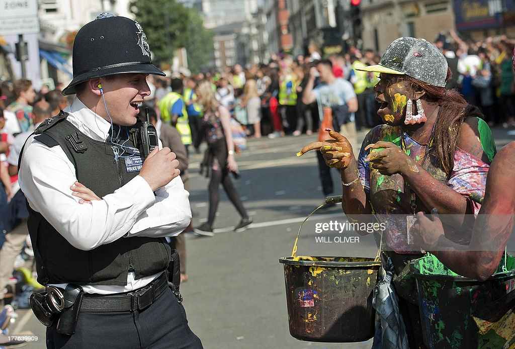 A performer chat with a police officer on the first day of the Notting Hill Carnival in west London on August 25, 2013. Running over two days, the Caribbean carnival puts on a Kid's day on the Sunday when costume prizes are awarded and a 'main parade' day on the Monday.