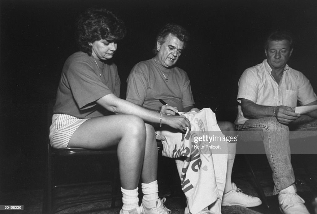 Performer Conway Twitty (C) signing his autograph on fan Virginia Byrne's sweat-shirt w. wife Dee sitting beside him.