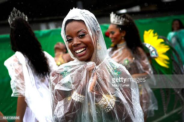 A performer dances on the streets in wearing ponchos over their colourful costumes during a rain soaked Notting Hill Carnival by on August 25th 2014...