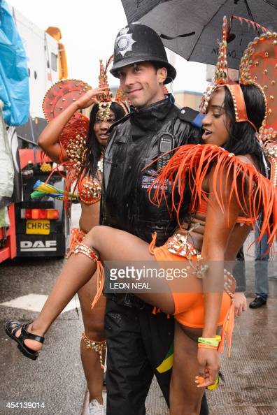 A performer dances with a police officer during the parade on the second day of the Notting Hill Carnival in west London on August 25 2014 Heavy rain...