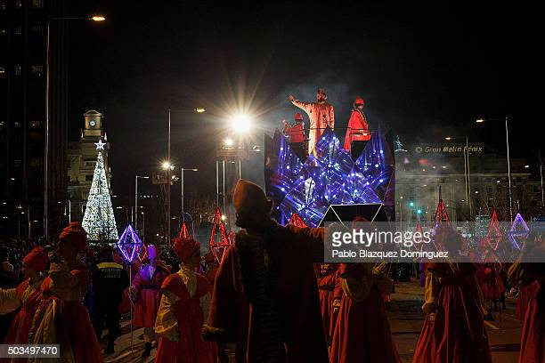 A performer dressed as Gaspar King waves his hand to the public as he rides a float during the 'Cabalgata de Reyes' or the Three Kings parade on...