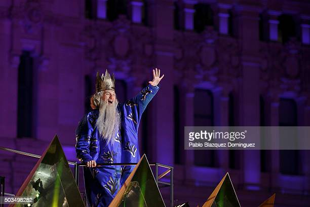 A performer dressed as Melchoir King waves his hand to the public as he rides a float during the 'Cabalgata de Reyes' or the Three Kings parade on...