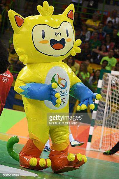 A performer dressed as Rio 2016 Olympic Games mascot Vinicius dances during a break of the men's preliminaries Group B handball match Brazil vs...