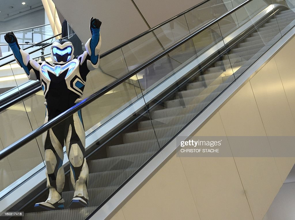 A performer dressed as robot stands at an escalator during the press preview of the international toy fair in Nuremberg, southern Germany, on January 29, 2013. Around 2.700 exhibitors show more than 1 million products at the international toy fair which opens its doors from January 29 to February 4, 2013.