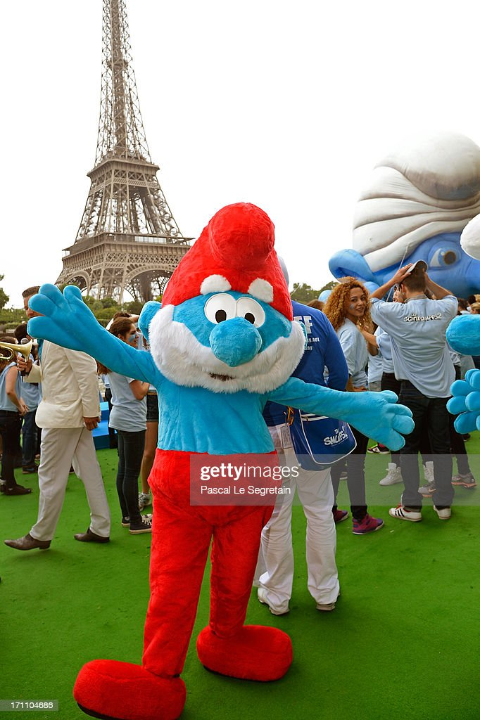 A performer dressed as the Smurf character 'Papa Smurf' takes part to a dance with performers as part of Global Smurfs Day celebrations on June 22, 2013 on the Seine river bank in Paris, France.