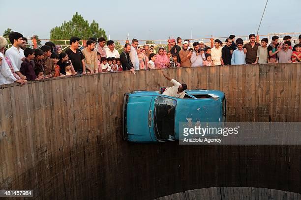 A performer drives a car on the Wall of Death at Nawaz Sharif Park in Rawalpindi Pakistan on July 20 2015