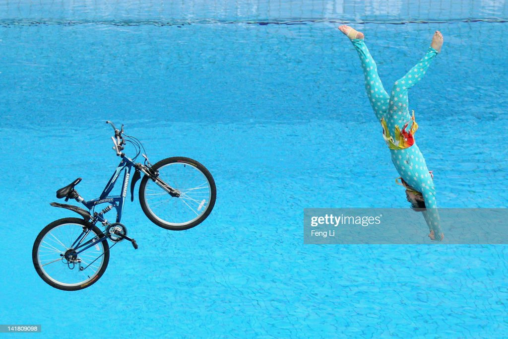 A performer falls with a bicycle after riding it off the 10m diving platform during day two of the FINA/Midea Diving World Series 2012 Beijing Station at the National aquatics center on March 24, 2012 in Beijing, China.