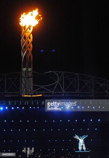 A performer floats on a snowboard while being propelled in the air by a giant fan in front of the Olympic cauldron just prior to its extinction...
