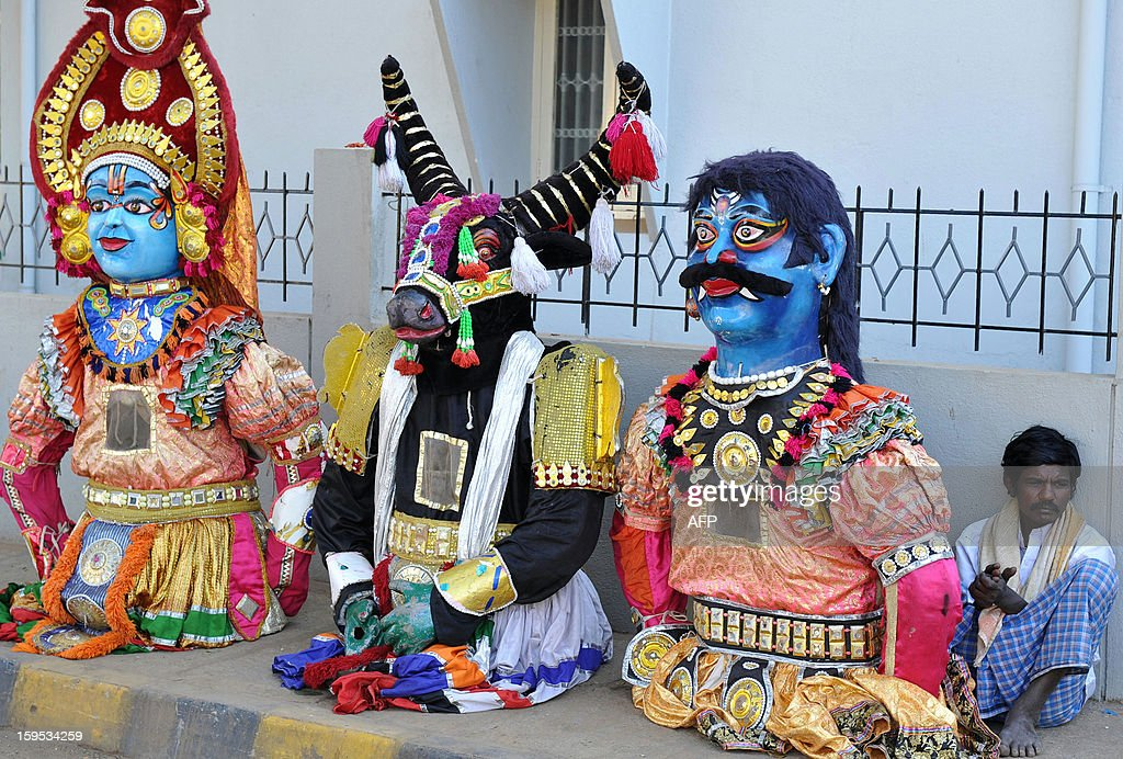A performer guards huge puppets prior to a performance in Bangalore, held as part of 'Sankranti' the Hindu harvest festival in the southern state of Karnataka on January 15, 2013. Sankranti is marked as the beginning of the month in the solar calendars followed in Tamil Nadu, Kerala, Andhra Pradesh, Karnataka, Orissa. AFP PHOTO/Manjunath KIRAN