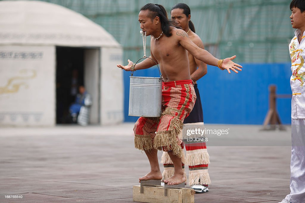 A performer holds a bucket of water with his teeth as he stands on knife blades during a show for tourists at Jiayuguan Fort in China's northwestern Gansu province on May 15, 2013. The fort marks the first pass at the west end of China's Great Wall, and is thougt to have been built in the Ming dynasty around 1372. One of the most intact passes on the Great Wall, the fort once signified the furthest reach of China, beyond which lay the Gobi desert and the plains of central Asia. AFP PHOTO / Ed Jones