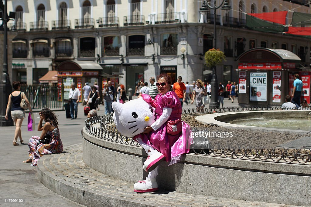 A performer in a costume takes a break in the Puerta del Sol on July 7, 2012 in Madrid, Spain. Despite having the fourth largest economy in the Eurozone, the economic situation in Spain remains troubled with their unemployment rate the highest of any Eurozone country. Spain is currently administering billions of euros of spending cuts and tax increases in a bid to manage its national debt. Spain also has access to loans of up to 100 billion euros from the European Financial Stability Facility which will be used to rescue the country's banks that have been badly affected by a crash in property prices.